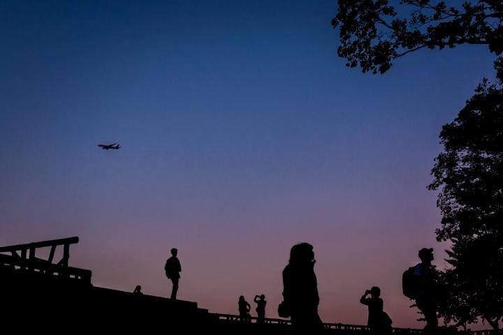 夕暮れ時に飛行機を撮る人々